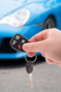 A hand holding car keys and a remote control for keyless entry.